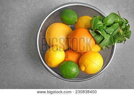 Colander with fruits on grey background