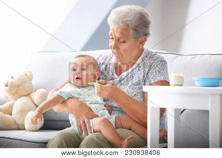 Senior woman feeding her little grandchild at home