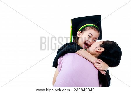 Kindergarten Graduation. Happy Asian Child In Graduation Gown Laughing. Mother Sitting And Hugging H