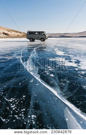 Travelling In Winter At Frozen Lake Baikal In Siberia, Russia. Tourist Van Parking On Ice With Crack