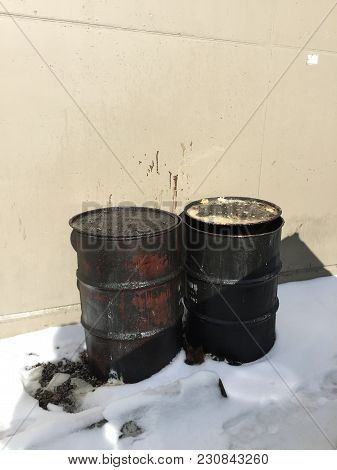 Closeup Of Two Dirty Greasy Barrels Outside Building In Snow.