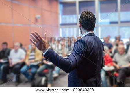 Rear View Of Speaker Giving A Talk At Business Meeting. Audience In The Conference Hall. Business An