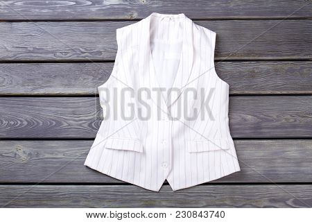 White Striped Sleeveless Jacket. Dark Wooden Desks Surface Background.