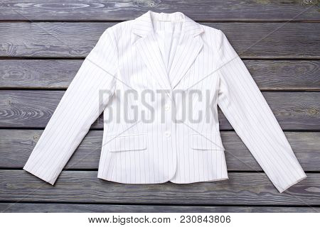 Flat Lay White Jacket On Dark Surface Background. Striped Vest, Top View Against Wooden Background.