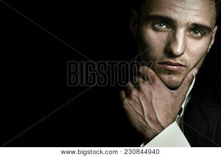 Handsome man face portrait with sexy blue eyes over dark black background