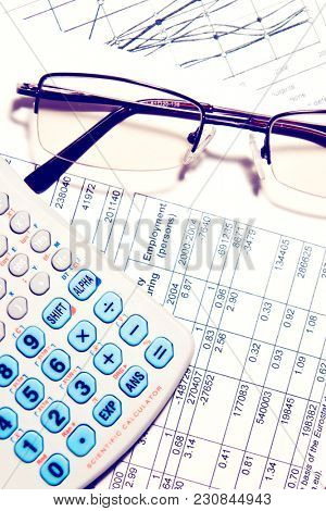 Business financial report chart with calculator and glasses. Tax, investment or banking concept