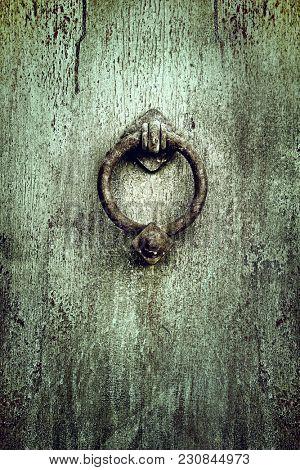 Old rusty knob or knocker on aged metallic retro door
