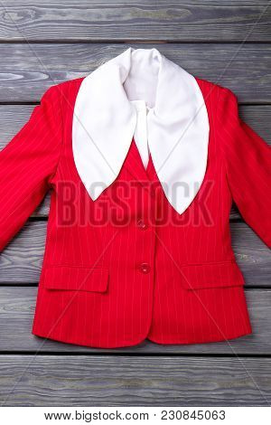Red Jacket With Big White Collar. Grey Wooden Surface Background.