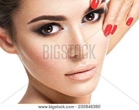 Portrait of young woman with red nails and brown makeup. Closeup portrait with a pretty female face.