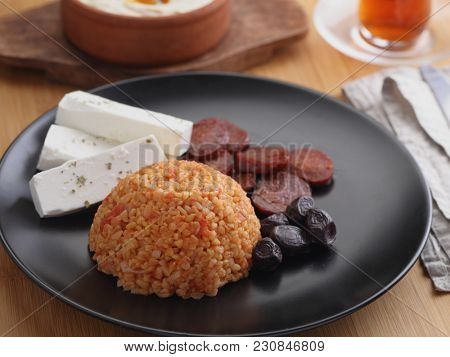 Turkish dinner with bulgur pilaf, sucuk sausages, feta cheese, and hot hummus
