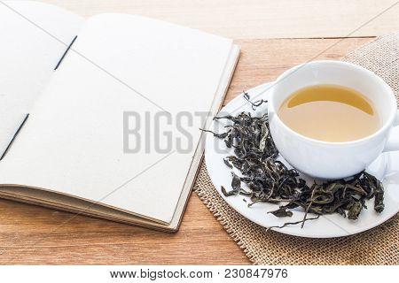 Cup Of Hot Tea On Sackcloth With Dried Tea Leaves And Handmade Book On Wooden Table With Copy Space