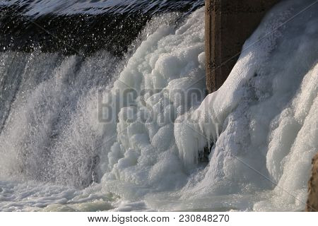 Dam, Waterfall. The Stream Of The River Falls From The Dam In The Winter. Icy Dam With A Strong Stre