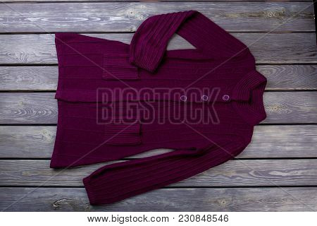 Flat Lay Purple Woman Cardigan. Wooden Desk Surface Background.
