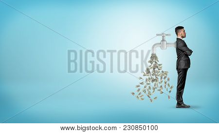 A Businessman Stands In A Side View With A Large Faucet Attached To His Back And Leaking Money Bills