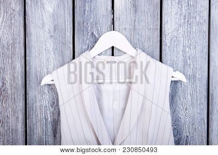 Close Up Clothing On Hanger. Top View, Wooden Desk Surface Background.