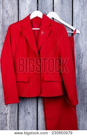 Red Woman Blazers. Business Jacket And Trousers. Top View, Wooden Surface Background.