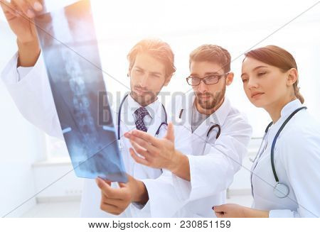 Three confident doctors examine an x-ray