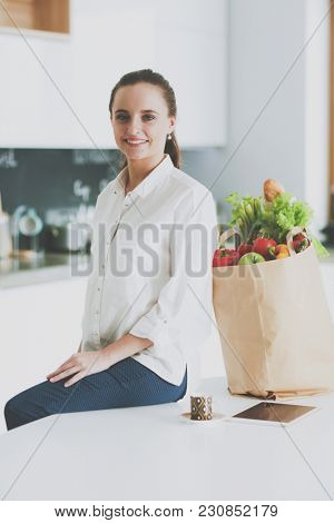 Young woman planning expenses and paying bills on her kitchen.
