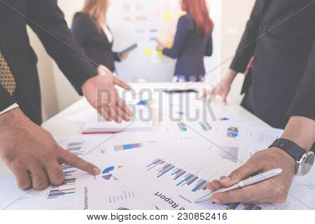 Hands Pointing On Data Chart Sheet For Business Meeting
