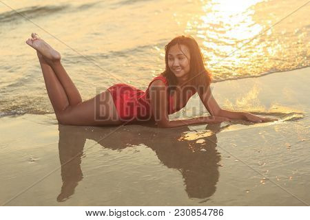 Beautiful Female Model Open Arms Under The Sunrise At Seaside. Sun Goes Under Horizon. Girl Stands A