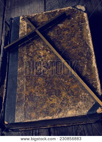 Old Ancient Book With A Brass Cross On A Rustic Wooden Monastery Table, Religion Concept Background