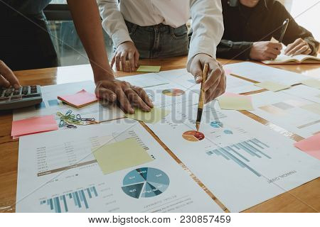 Close Up Hand Of Woman Holding Pen Pointing Financial Document. Group Of Business People Having Meet