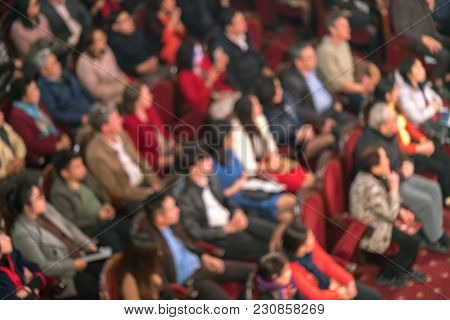 Blurred Audience In A Theater, On A Concert. Viewers Watching The Show.