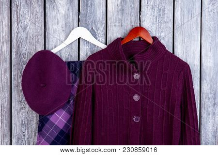 Purple Winter Outfits For Girls. Flat Lay, Wool Cardigan, Hat And Skirt. Dark Wooden Desk Surface Ba