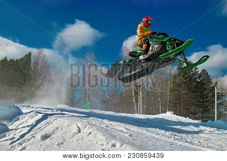 Big Green Sport Snowmobile Jump. Cloud Of Snow Dust From Under Snowmobile Tracks. Concept Extreme Re