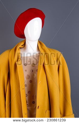 Mannequin With Women Winter Clothes. Yellow Wool Coat, Beige Blouse And Red Beret Hat. Black Backgro