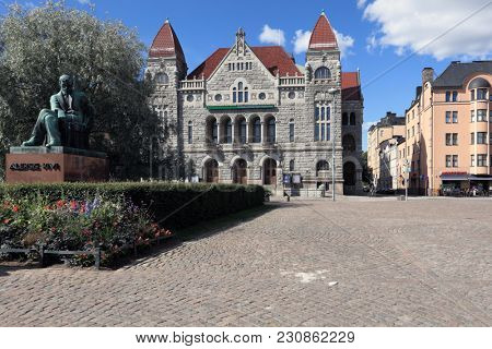 HELSINKI, FINLAND - JULY 15, 2017: Monument to Finnish writer Aleksis Kivi in front of Finnish National Theater. Created in 1872, the theater is hosted in that building since 1902