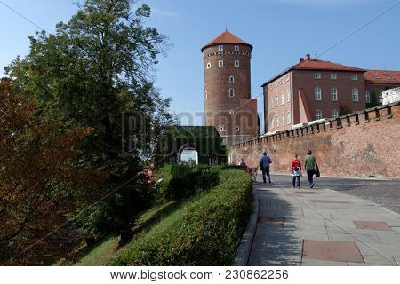 KRAKOW, POLAND - SEPTEMBER 15, 2013: People on the street under Senator tower of Wawel royal castle. The tower was built in the mid-fifteenth century, and later restored several times