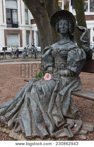 THE HAGUE, NETHERLANDS - JANUARY 3, 2017: Statue Lady On Bench on Anna Paulownastraat in the Hague. The statue was created in 1999 by Alexander Taratynov and depicting Queen Anna of the Netherlands