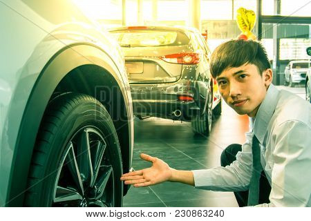 Asian Man Business With Wheels And Car Suspension Blurry Background.for Automotive Or Transportation