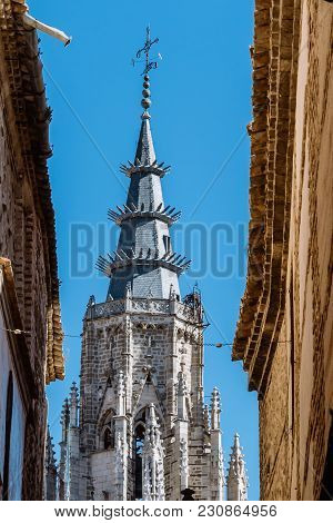 Picturesque View Of The Tower Of The Cathedral Of Toledo Framed By Old Buildings In Jewish Quarter.