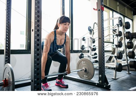 Woman Doing Deadlift In The Smith Machine