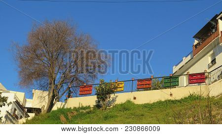 Flower Pots And Colorful Painted Wooden Pallets On Fence In Alora Village, Andalusia - Spain