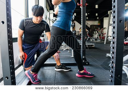 Woman Doing Lunge With Personal Trainer