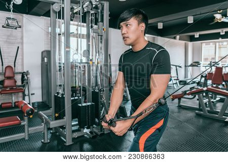 Young Asian Man Working Out At The Gym Doing Chest Fly Exercises On The Cable Wire Machine.