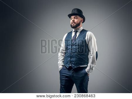 Portrait Of Elegant Bearded Male Dressed In A Waistcoat And A Cylinder Hat In Grey Vignette Backgrou