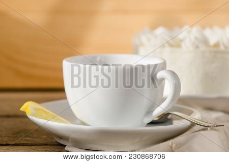 White Cup Of Tea With A Saucer, With A Lemon In The Sun Is On A Wooden Table With A Cake
