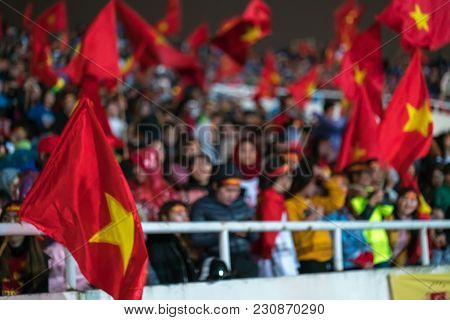 Blurred Background Of Crowd Of Vietnamese Football Fans At My Dinh Stadium. Supporter With Red Cloth