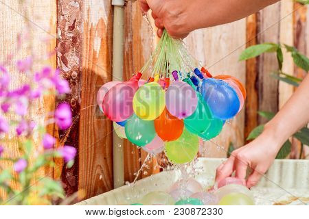 Filling Colorful  Water Balloons With Water In The Open Air