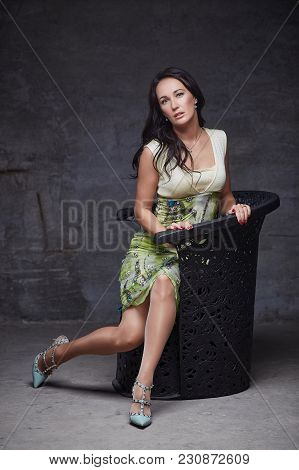 Brunette Woman In A Dress Sitting On The Chair.