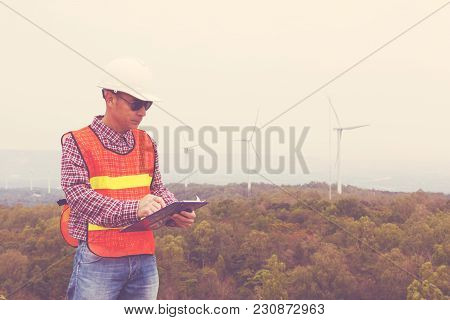 Electric Engineer Writing Maintenance Report On Clipboard