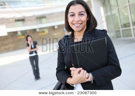 An attractive hispanic business worker with co-worker in background