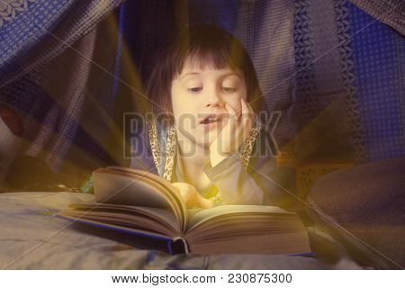 Cute Little Child Girl Reading A Book In Bed Before Going To Sleep (bedtime, Childhood, Safety Conce
