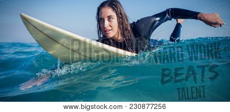 Hard work beats talent against woman in wetsuit with a surfboard on a sunny day