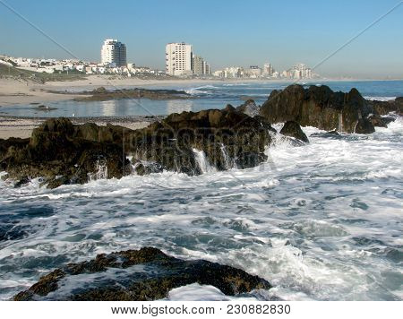 A Rough Sea In Fore Ground, Washing Over Some Rocks, With High Rise Buildings In The Back Ground