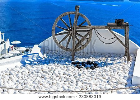 Ancient Wooden Wheel And White Painted Pebbles Against Blue Aegean Sea In Santorini (oia), Greek Isl